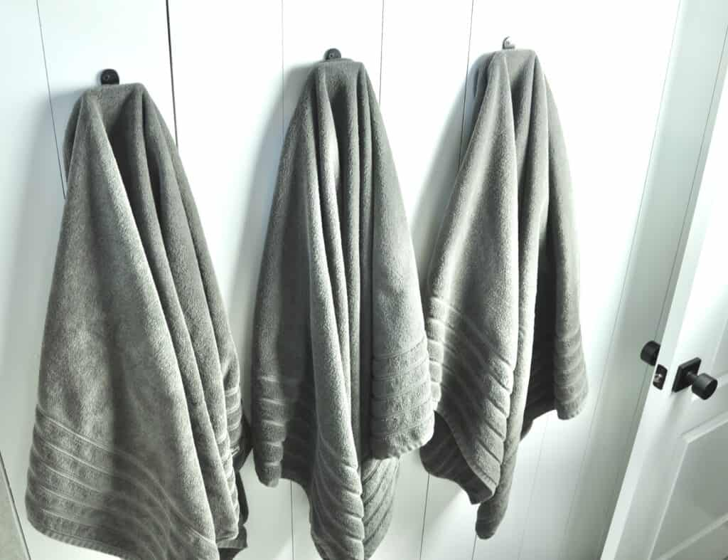 gray Lacoste towels on bathroom hooks with vertical shiplap wall
