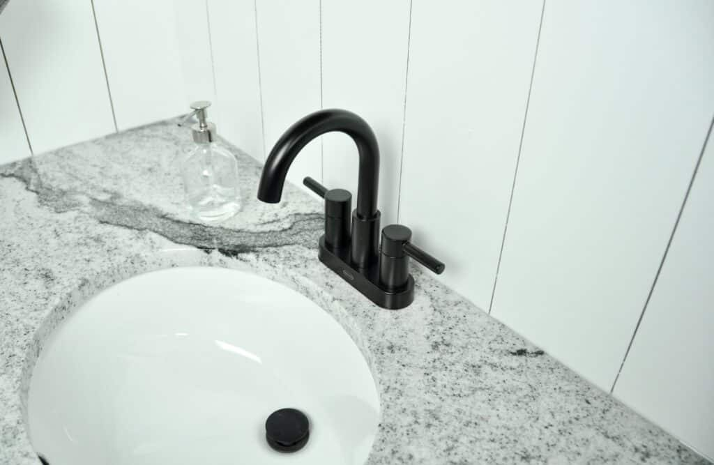 mat black bathroom faucet with shiplap wood detail